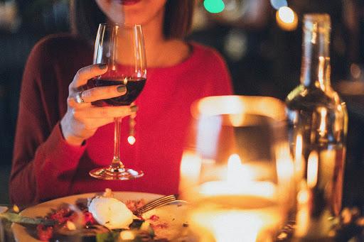 Mulher tomando vinho em jantar romântico