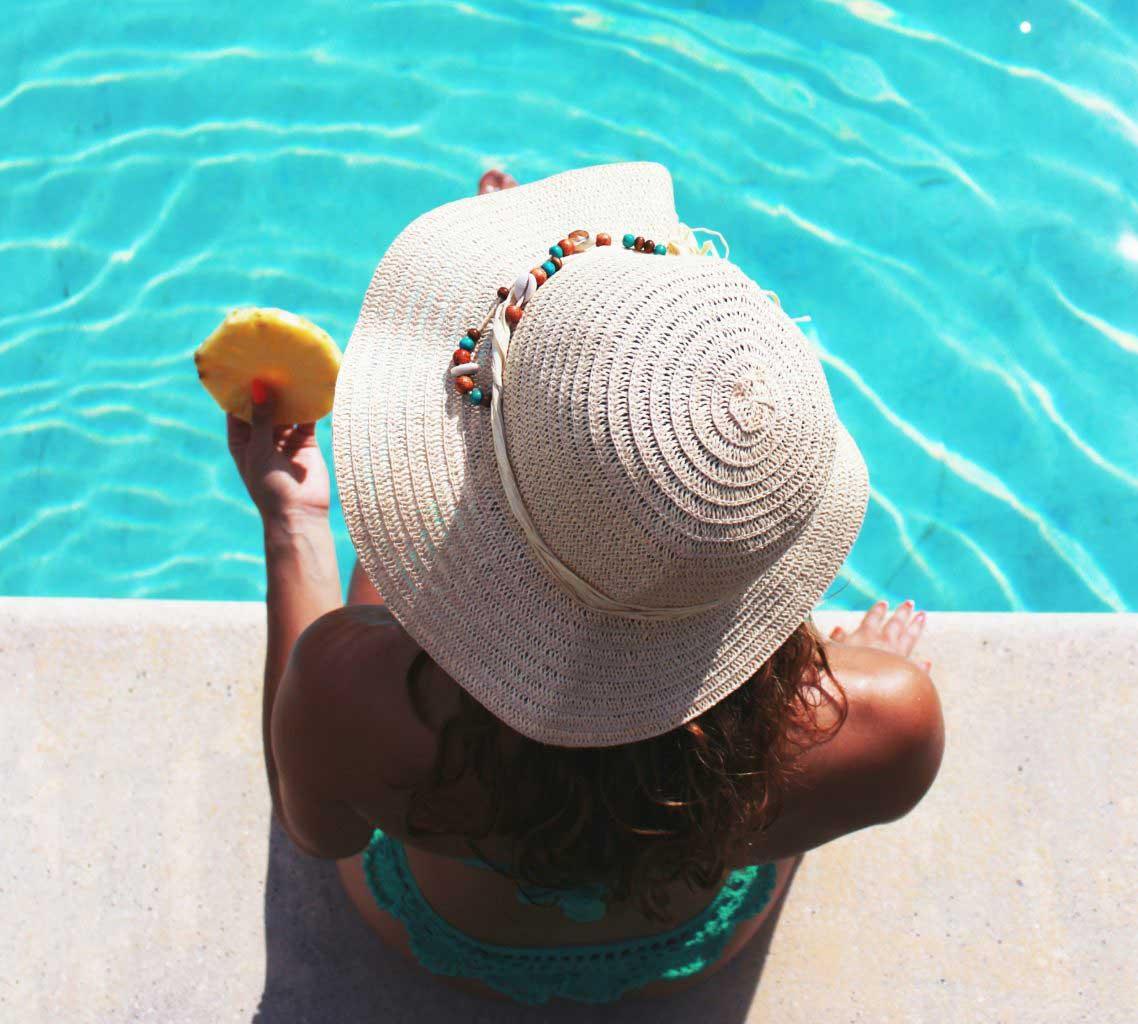 Mulher sentada na beira da piscina do Hotel Del Rey Foz