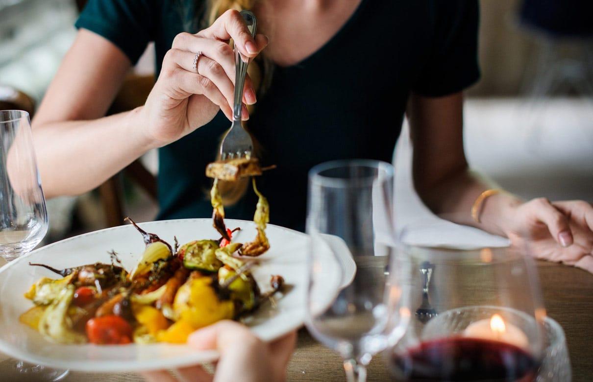 Mulher comendo em restaurante vegetariano