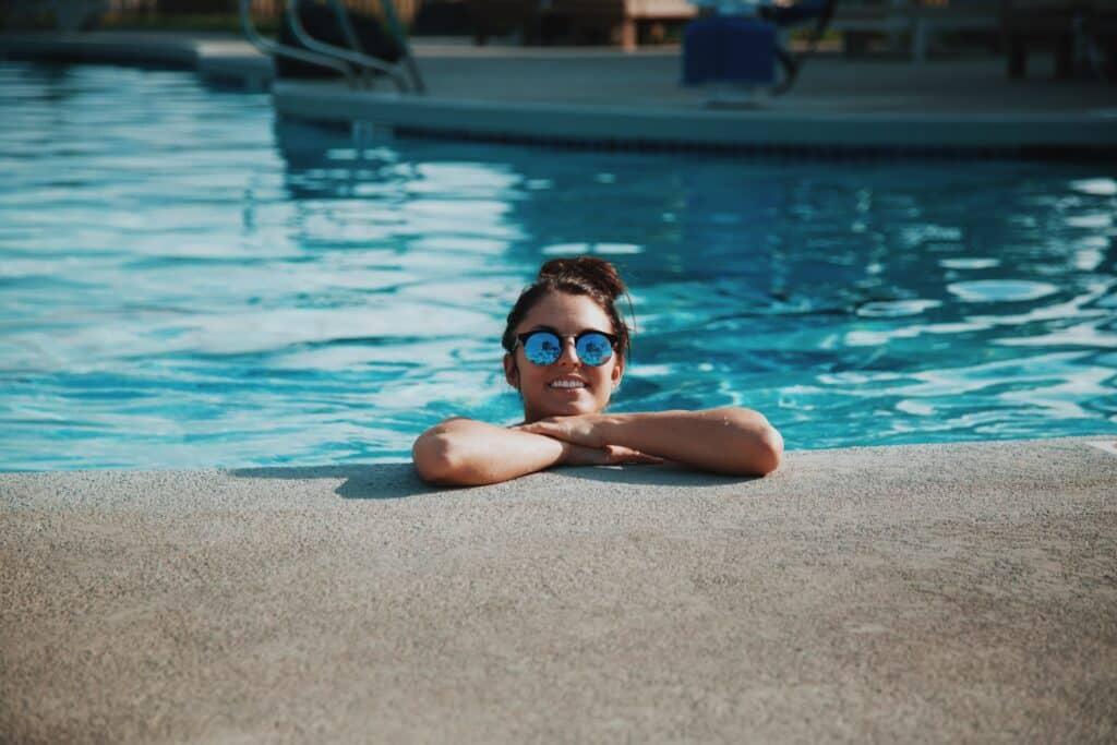 Mulher de óculos escuro, sorrindo na beira da piscina