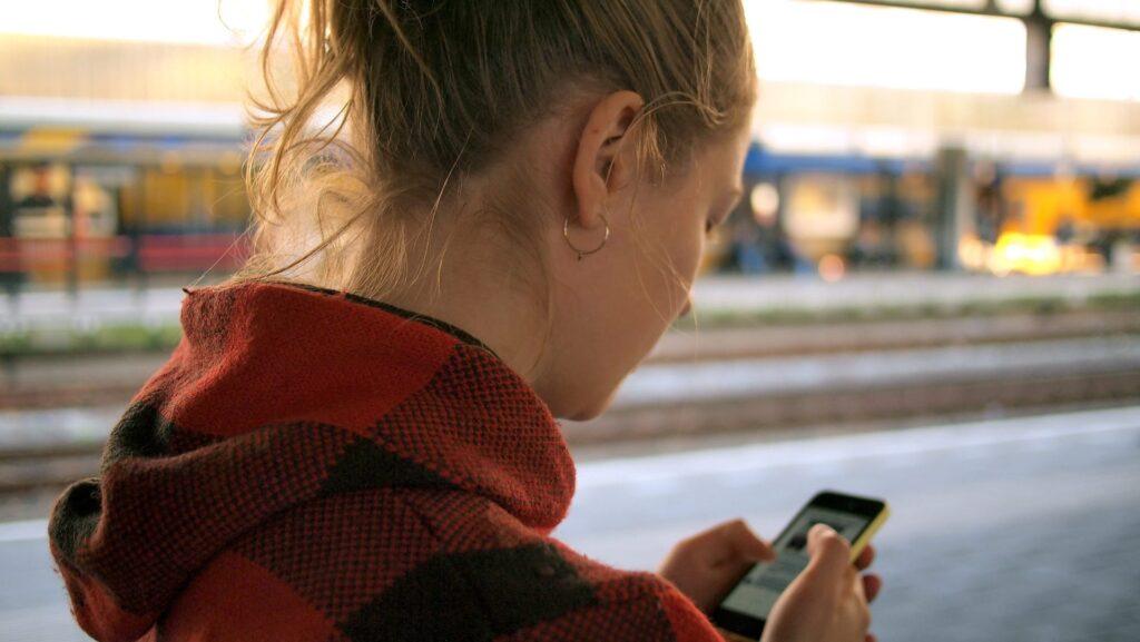 Mulher usando aplicativo de viagem no celular