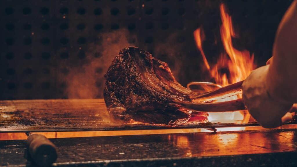 Pessoa assando carne na churrasqueira