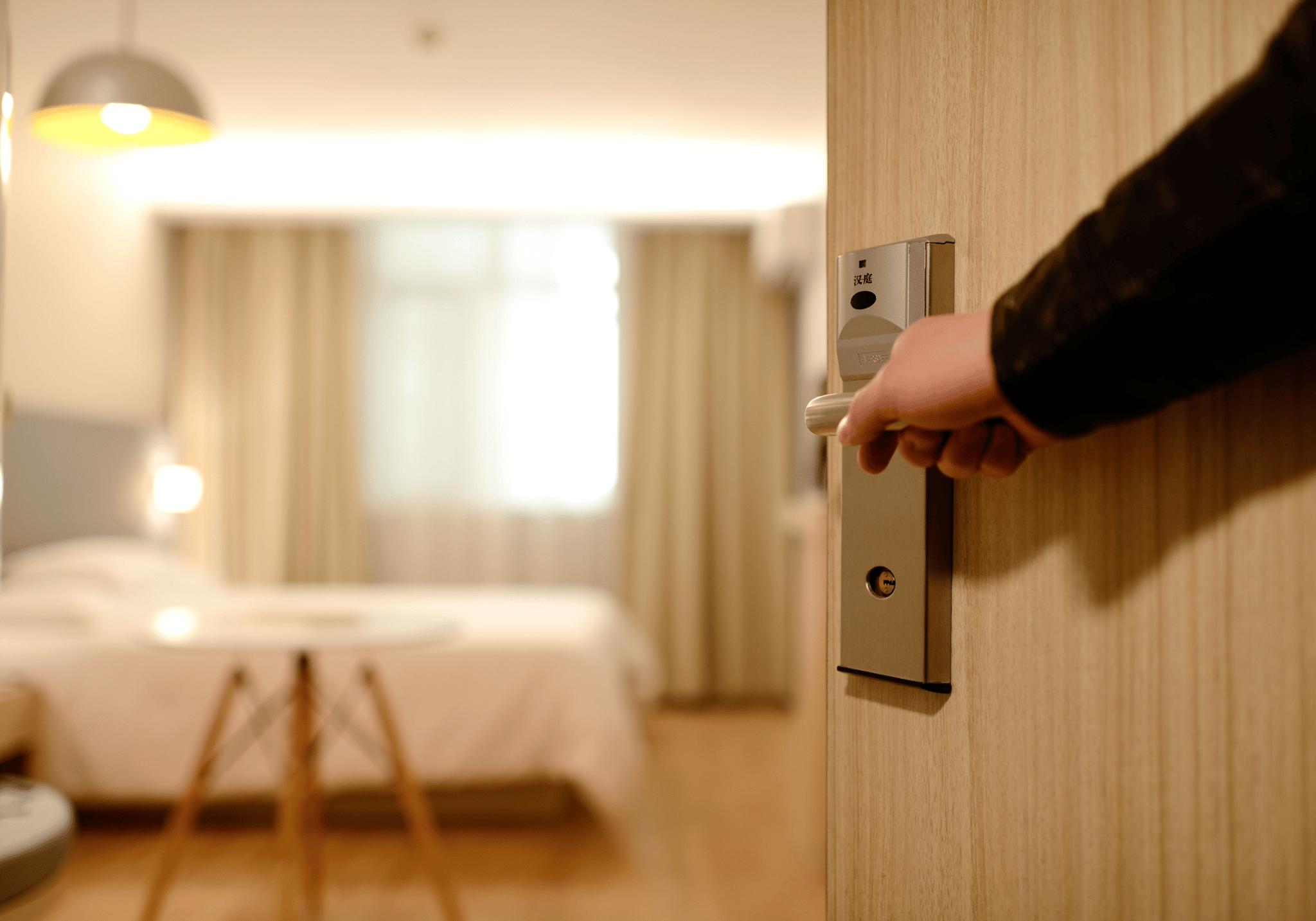 Pessoa abrindo porta do quarto de hotel