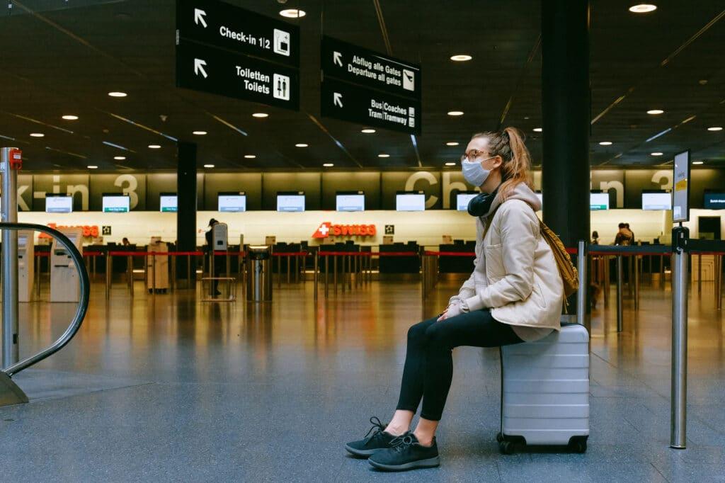 Mulher de máscara esperando voo em aeroporto
