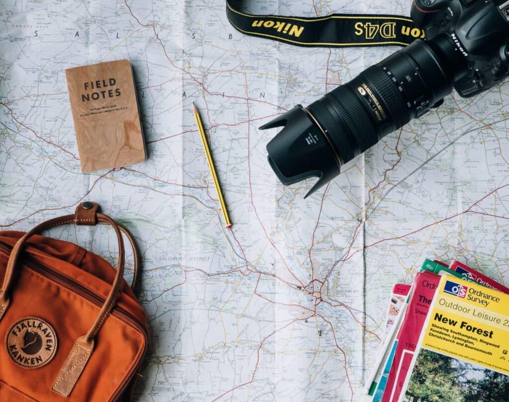 Mapa de viagem aberto com câmera, guias e lápis em cima